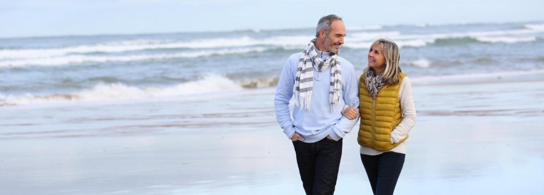 Man en vrouw lopen op het strand