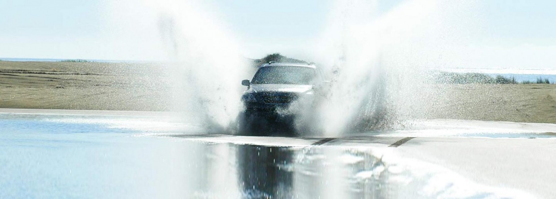 Auto rijdt door een plas met water