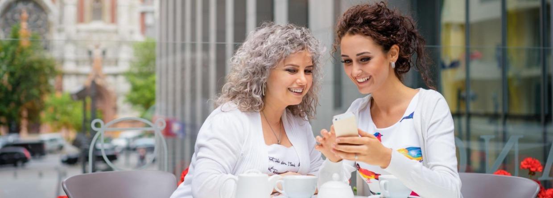 Moeder en dochter drinken koffie bij een restaurant