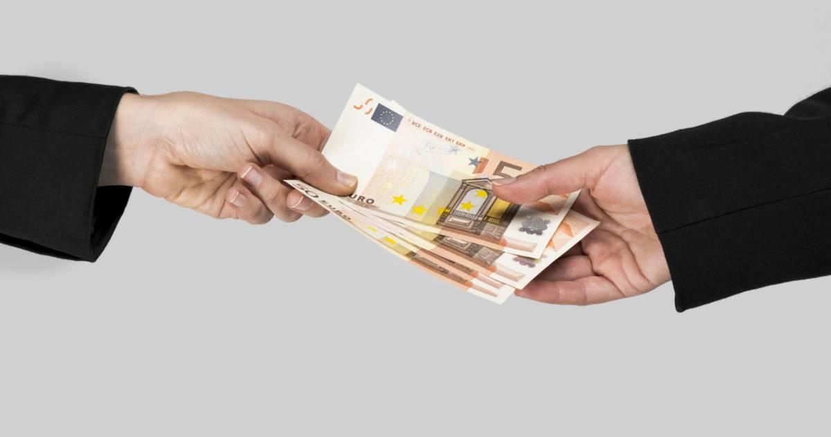 Twee handen die geld aan elkaar geven