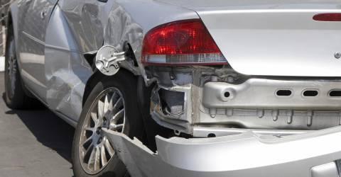 Grijze auto met schade aan de linker achterkant