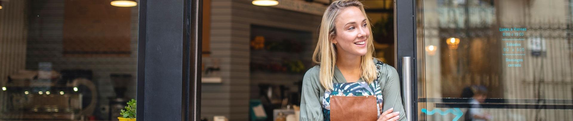 Jonge cafe eigenaar staat met haar armen gekruist bij de voordeur
