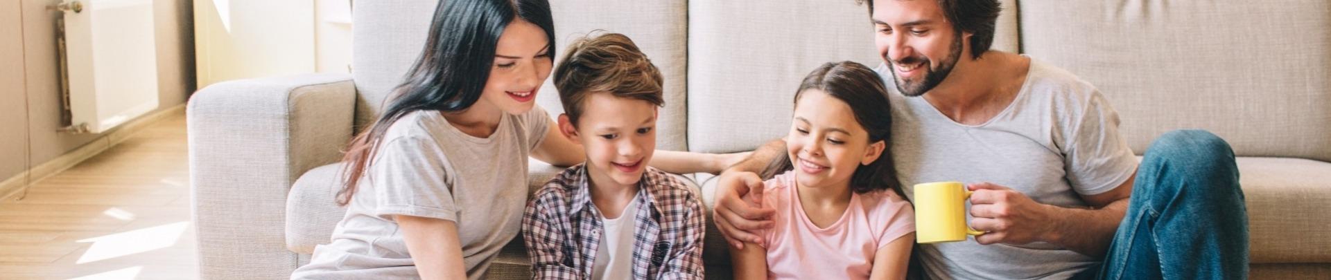 Familie, 2 ouders, 2 kinderen lezen samen in een boek